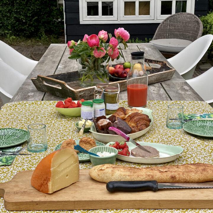 Ontbijt met stokbrood, sap, croissantjes, kaas in de ochtendzon