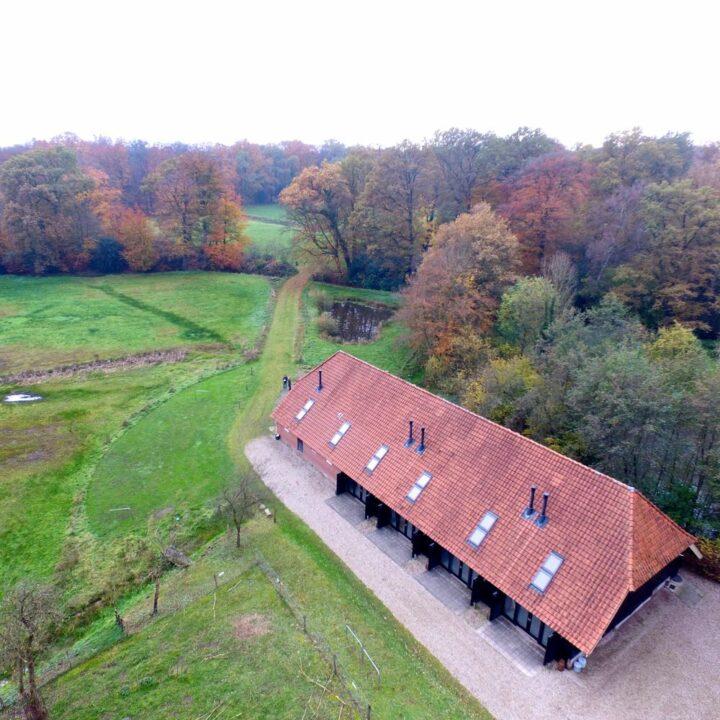 Luchtfoto van de schuur met boerderijlodges op Landgoed Twickel
