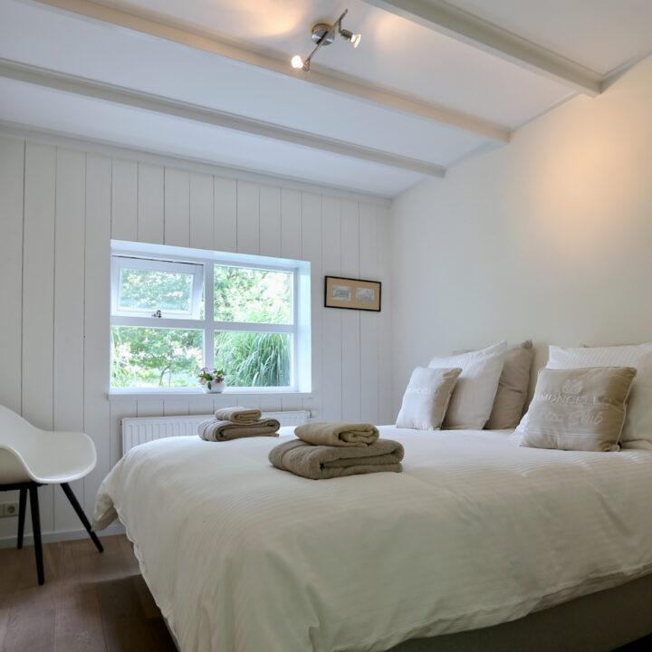 Slaapkamer met opgemaakt tweepersoons bed met luxe beddengoed