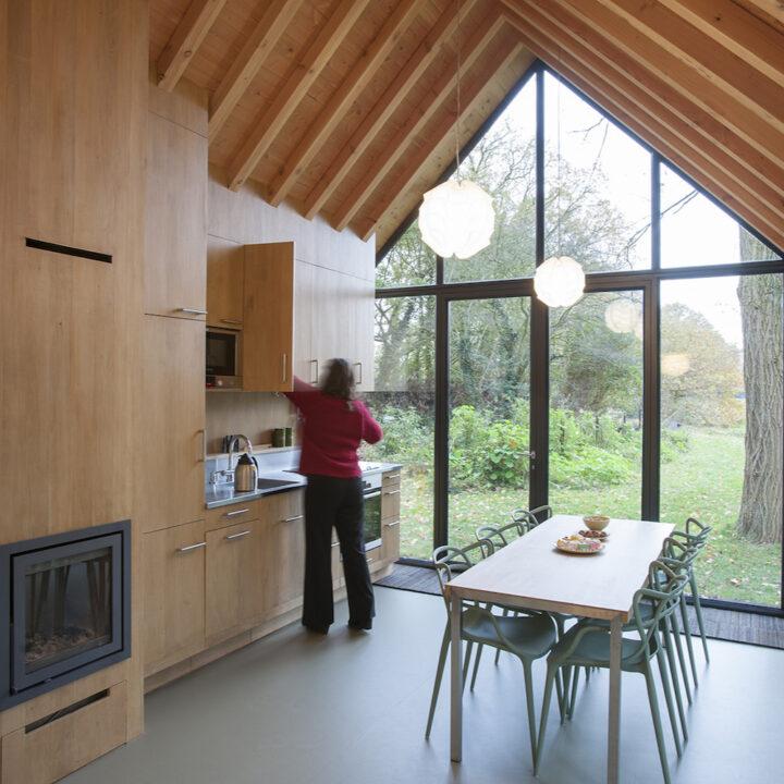 Dame in de keuken van een design vakantiehuis met grote glazen gevel