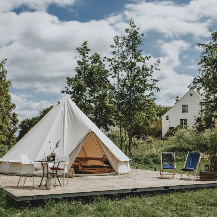 Glamping tent met ligstoelen en een tafel met stoelen bij slot Doddendael