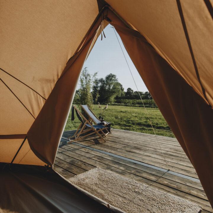 Doorkijkje vanuit de tent op twee ligstoelen en de weide