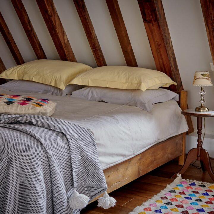Opgemaakt bed onder een schuin dak