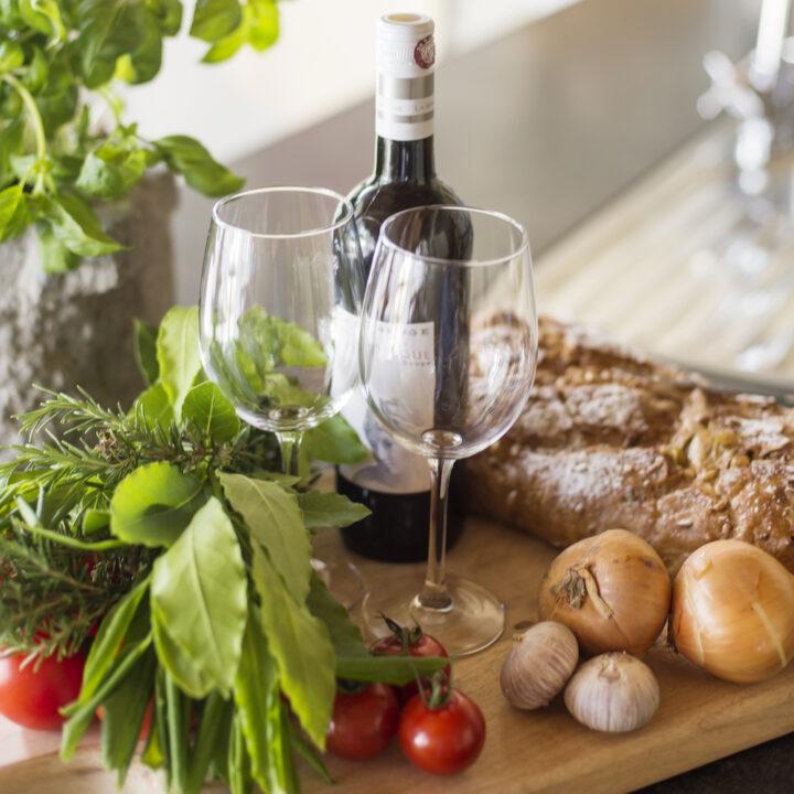 Plank met wijnfles, glazen, brood en tomaatjes