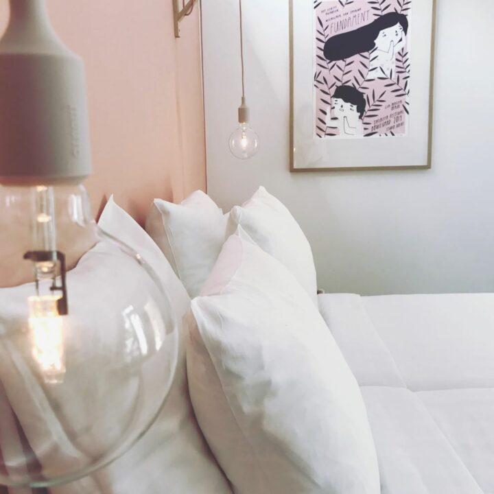 Slaapkamer met zachte tinten en wit opgemaakt bed