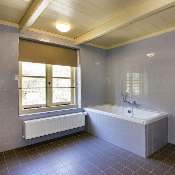 Ruime badkamer met ligbad in de gasterij