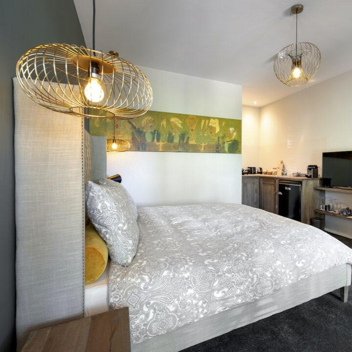 Slaapkamer met keukenblokje en televisie bij het bed
