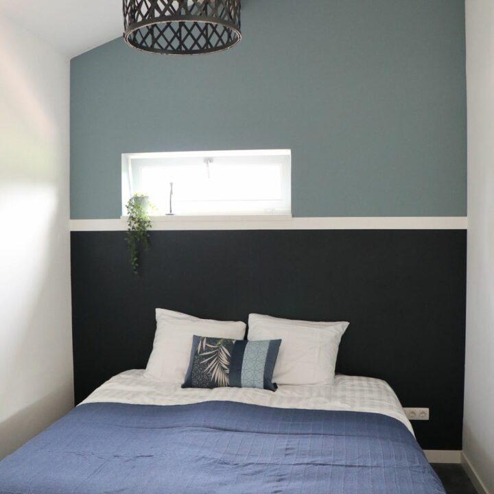 Slaapkamer met blauw grijze wand en bed met blauwe sprei