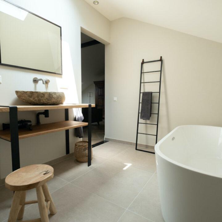 Badkamer met design bad met metalen trapje tegen de wand