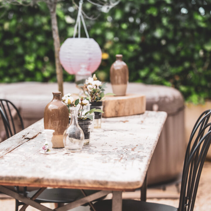 Tafel in de tuin met karaffen en bloemen bij het vakantiehuis in Frankrijk