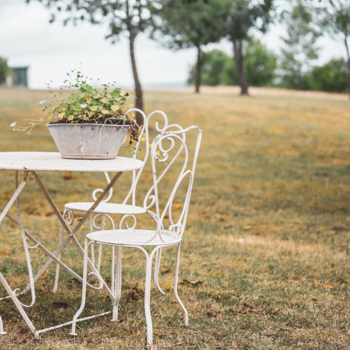 Witte gietijzeren stoeltjes van het gras