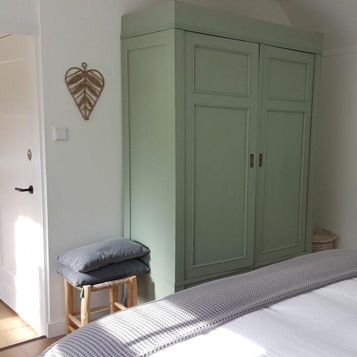 Slaapkamer met zachtgroene kledingkast
