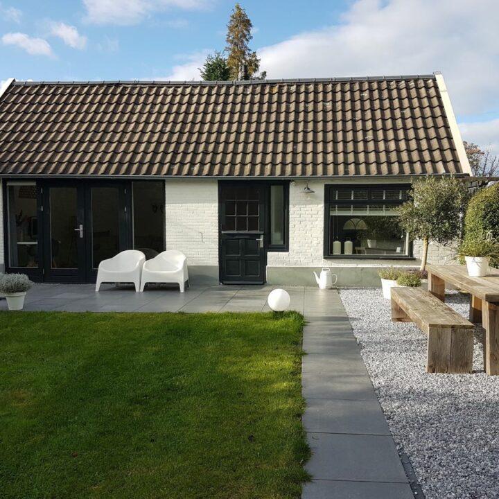 Huisje met tuin met witte stoelen en steigerhouten tafel met banken
