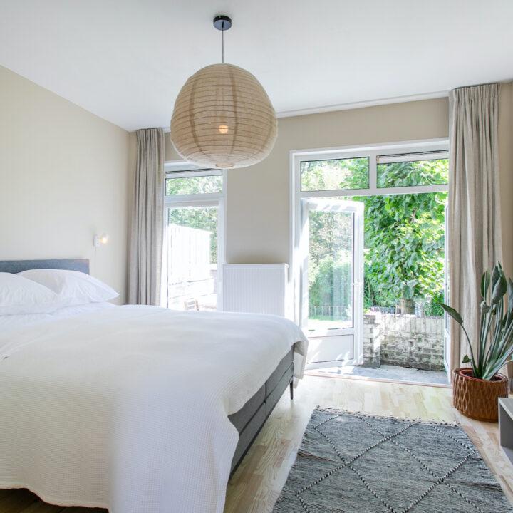 Slaapkamer met openslaande tuindeuren in de B&B in Amsterdam