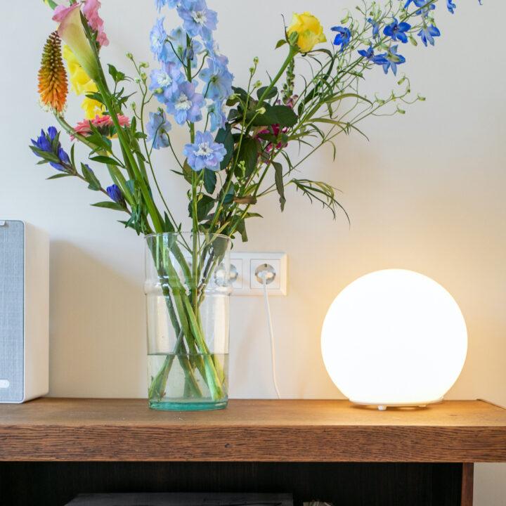 Bloemen in de vaas naast een bol lamp