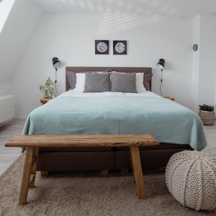 Slaapkamer met houten bankje aan het voeteneinde van het bed
