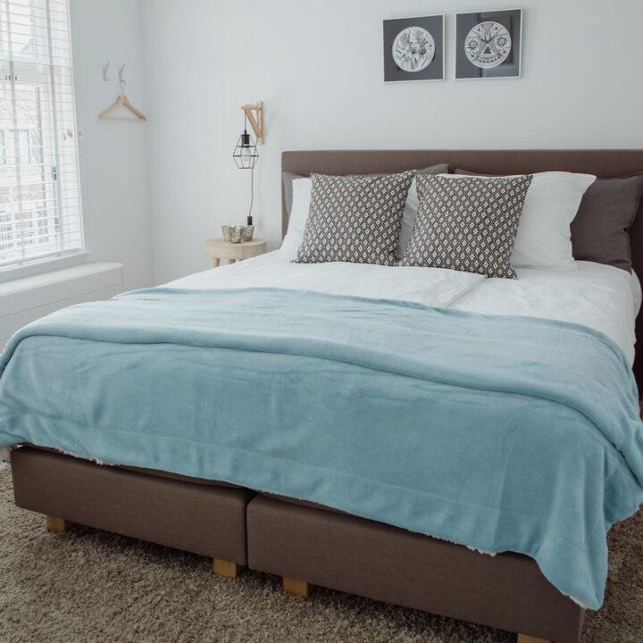 Comfortabel bed met ijsblauwe sprei