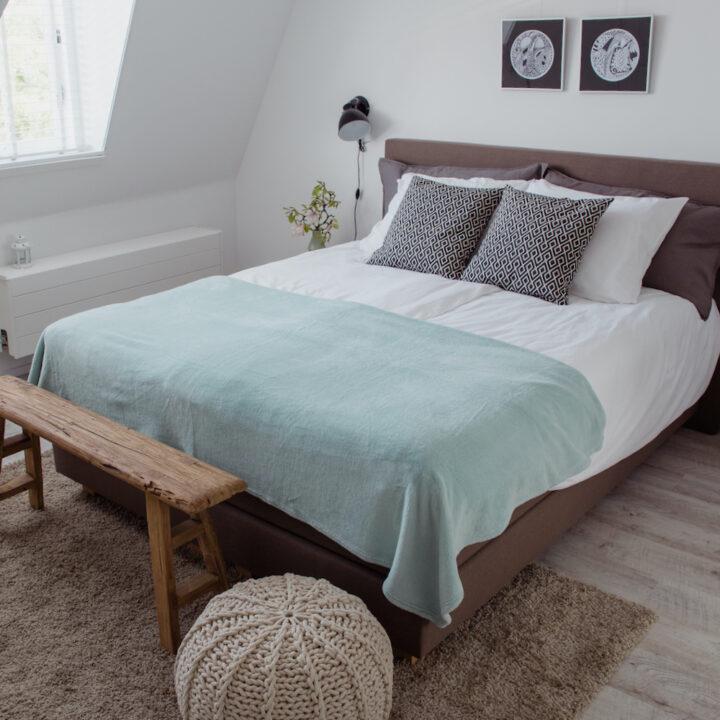 B&B kamer met poef en fris opgemaakt bed