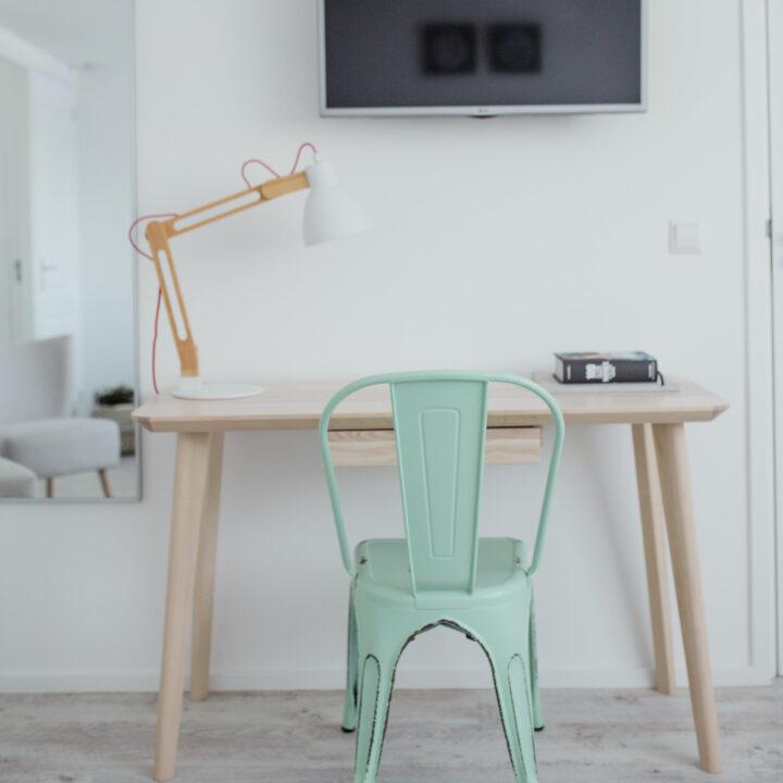 Mintgroene stoel bij een tafel met bureaulamp