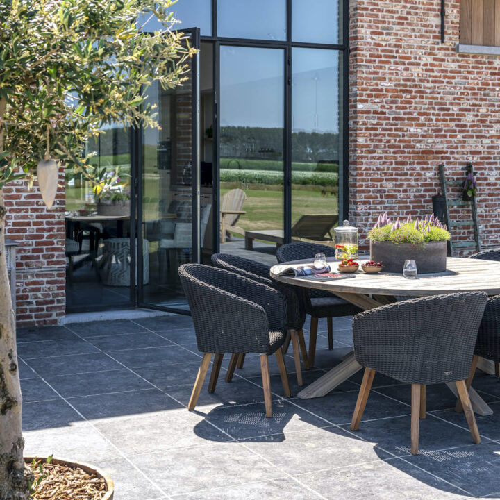 Ronde tafel met rotan fauteuils op het terras