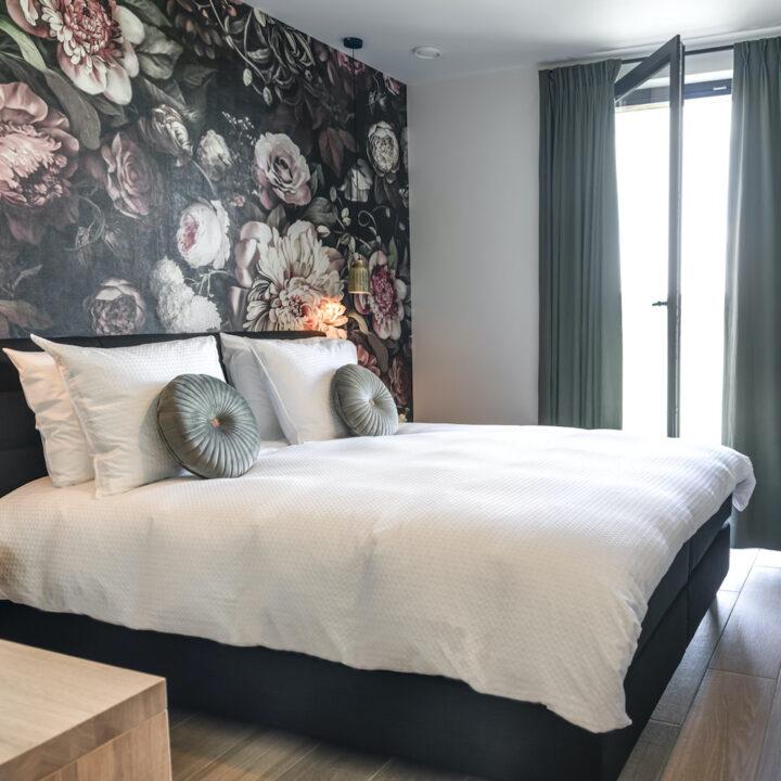 Bloemenbehang boven het comfortabele bed