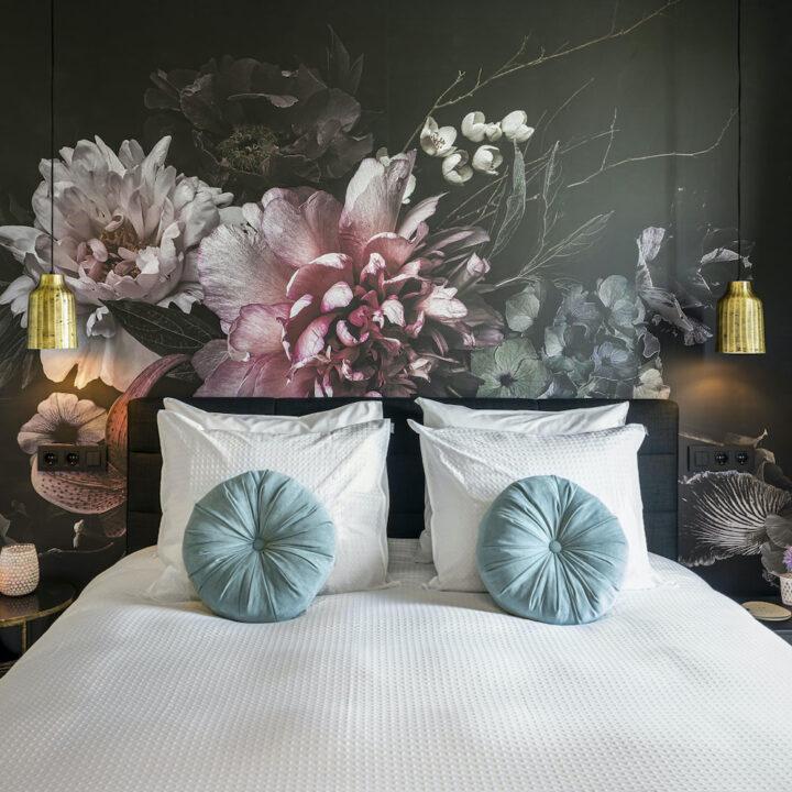Tweepersoons bed met aan het hoofd bloemenbehang