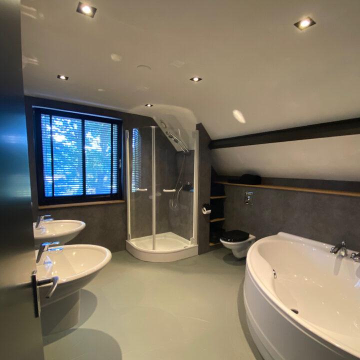 Badkamer met bad en douche in de villa