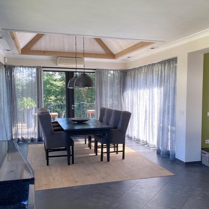 Eettafel met 6 comfortabele fauteuils in de glazen uitbouw
