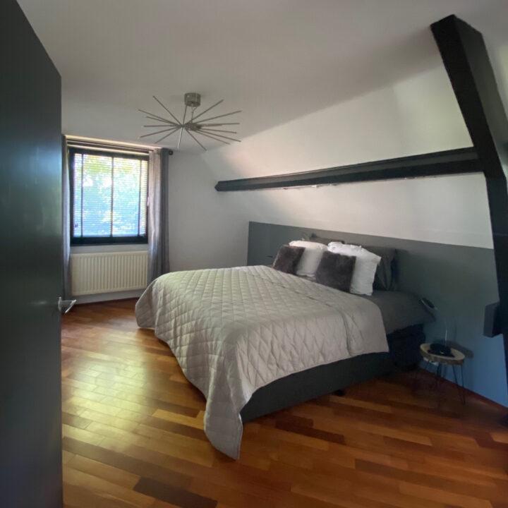 Slaapkamer met grijze sprei en kussens op bed