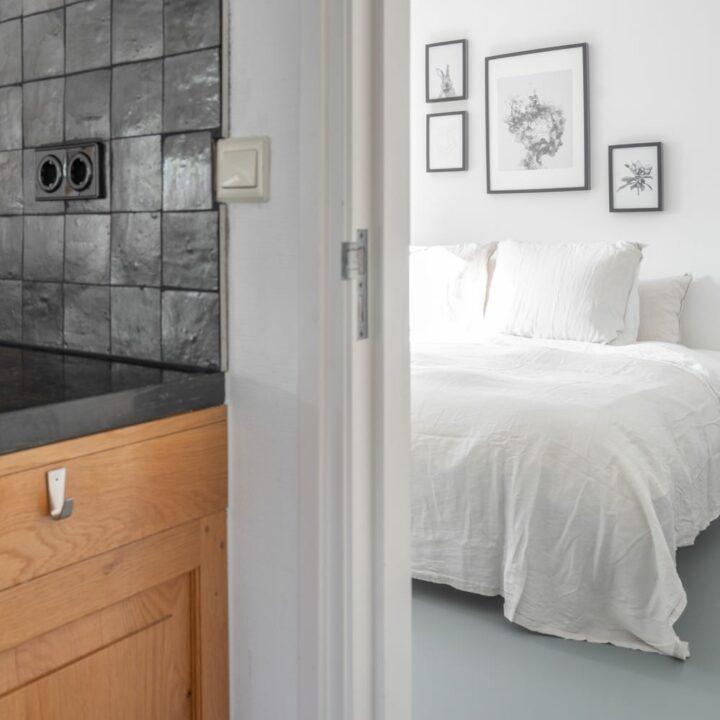 Slaapkamer met wit bed en zwart wit lijstjes boven het bed