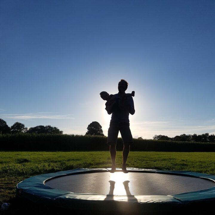 Vader en kind op de trampoline