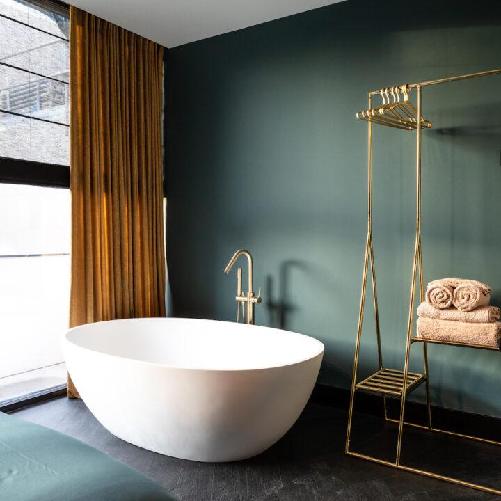 Vrijstaand design bad met groene wand in het boutique hotel