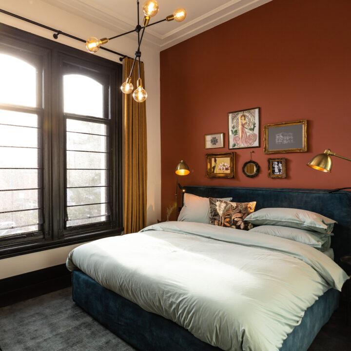 Luxe suite met roodbruine wand en lijstjes boven het bed in het boutique hotel