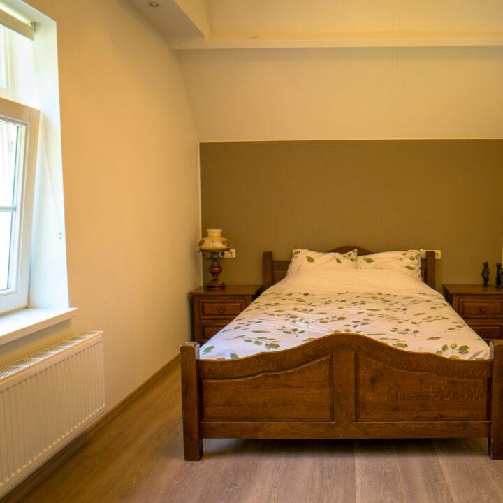 Slaapkamer met antiek bed in het vakantiehuis in Zeeland