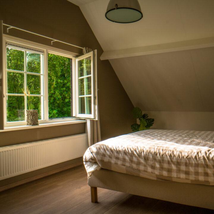Slaapkamer met openstaand raam in het vakantiehuis in Zeeland