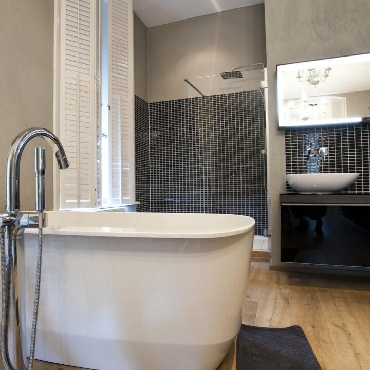 Bad in badkamer met inloopdouche met zwarte tegeltjes
