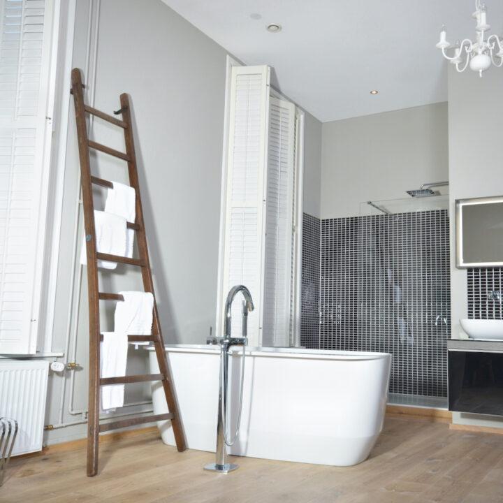 Wit vrijstaand bad met houten trap met handdoeken erop
