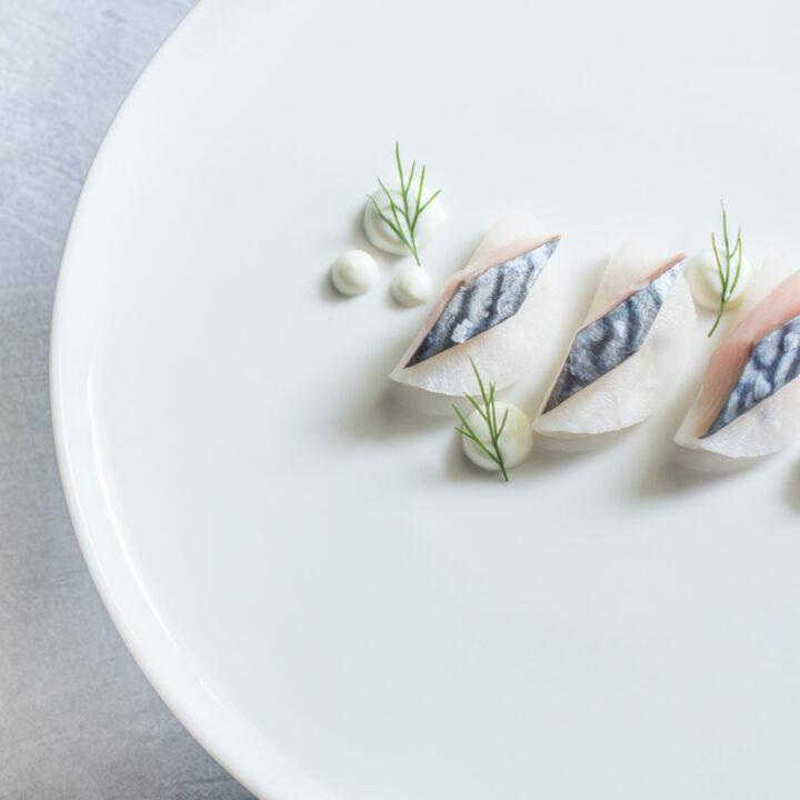 Wit bord met voorgerecht met drie stukjes vis
