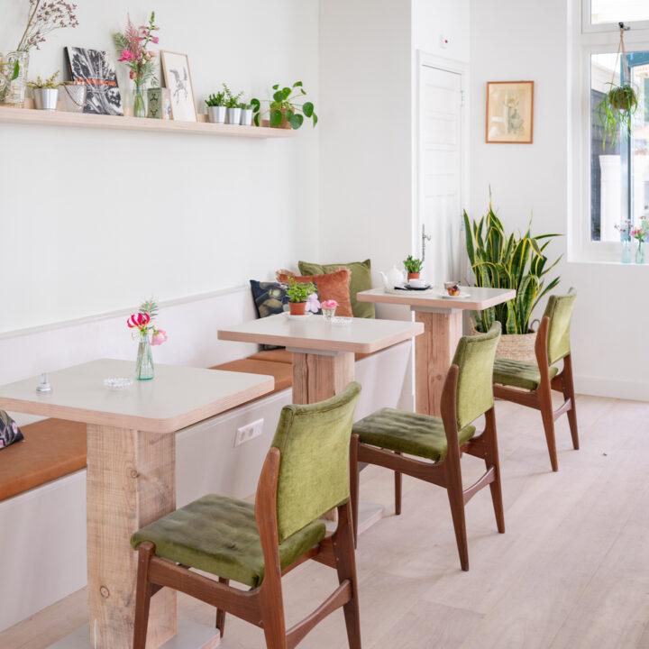 Rijtje tafels met groen fluwelen stoelen in boutique hotel de Stadsherberg