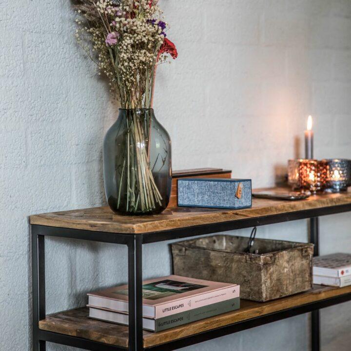 Side table met vaas bloemen en boeken en brandende kaarsen