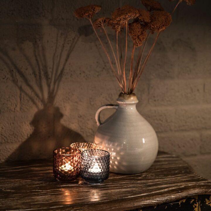 Vaas met droogbloemen en brandende kaarsjes