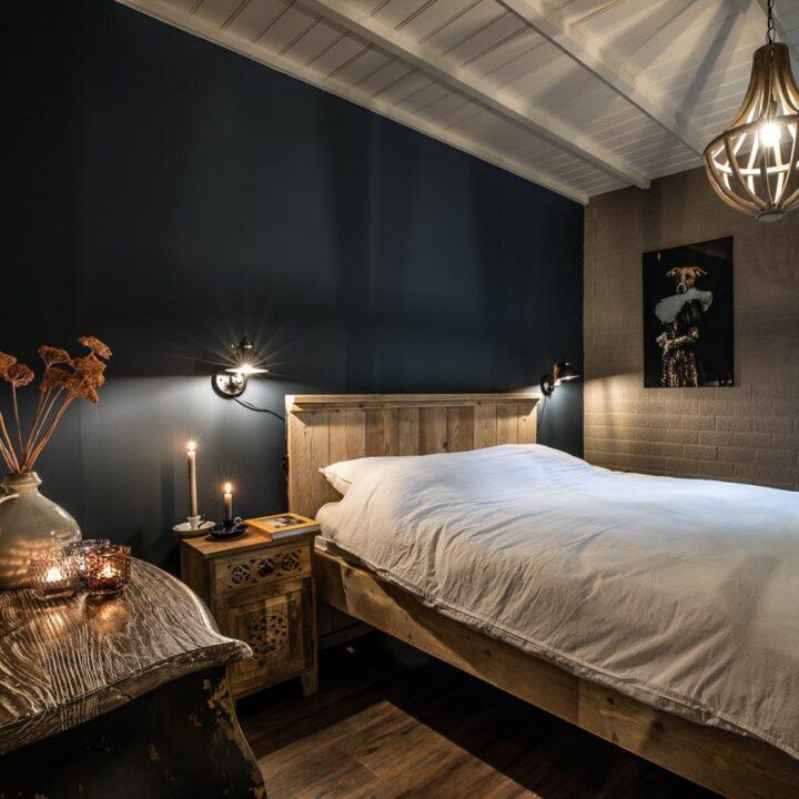 Slaapkamer met zwarte wand en houten details