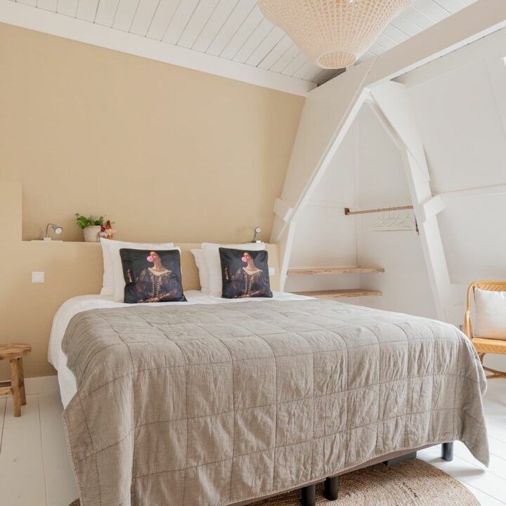 Hotelkamer met groot bed en kussens met een grootmeester erop