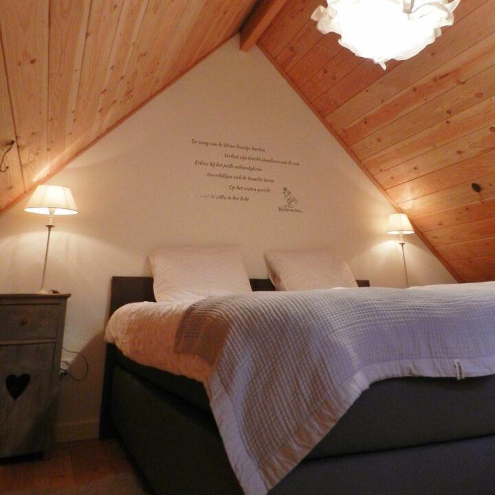 Slaapkamer in het tiny house, met tekst boven de muur