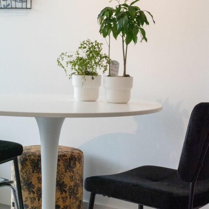 Witte ronde tafel met zwarte fauteuils