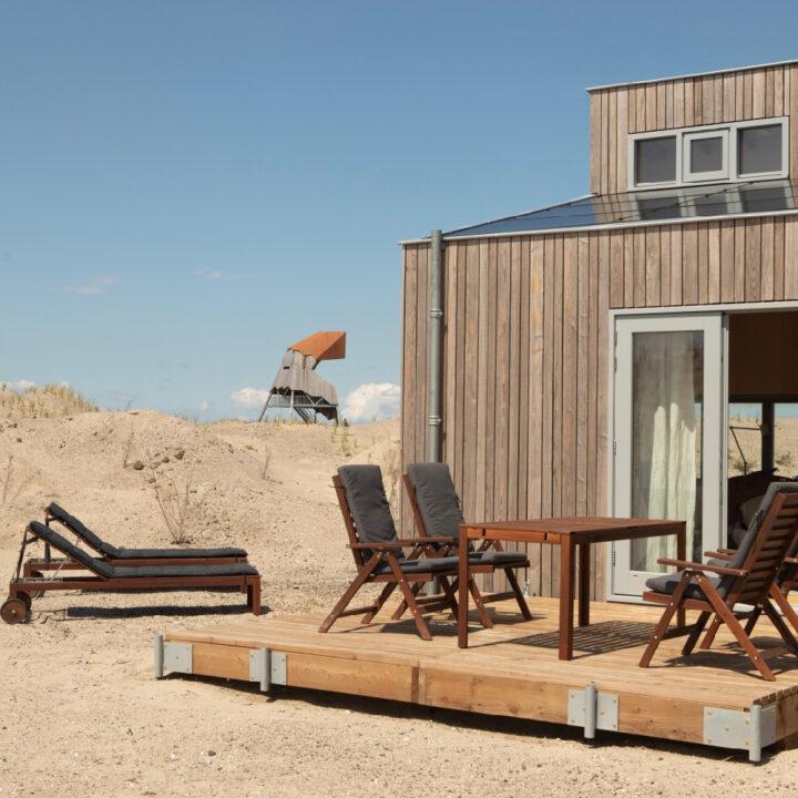 Terras met ligstoelen in het zand en houten tuinmeubilair