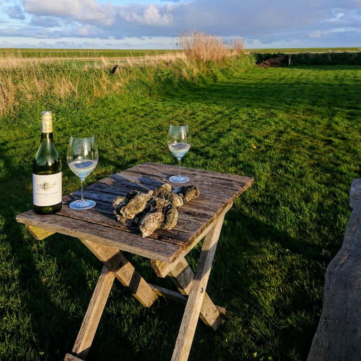 Tafeltje met oesters en wijnglazen aan de rand van de Wadden