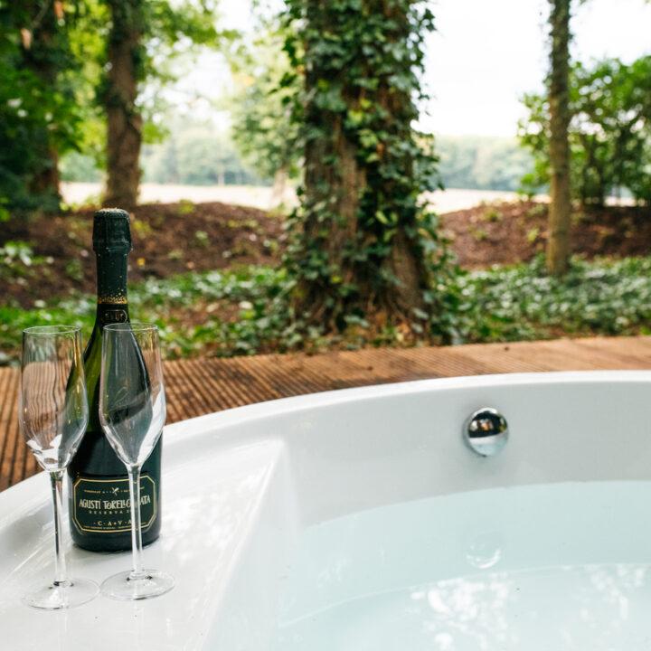Buiten bad met flesje bubbels op de rand
