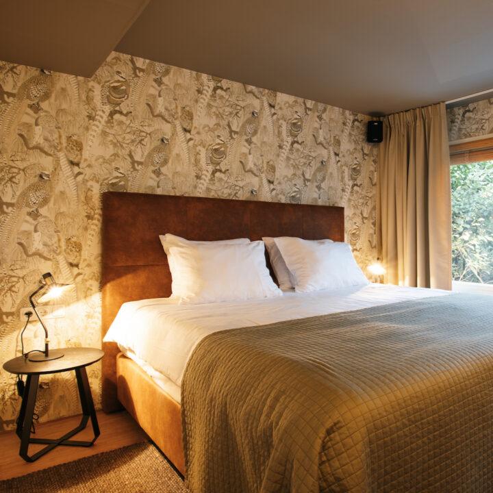 Slaapkamer met fazanten behang in de boshut