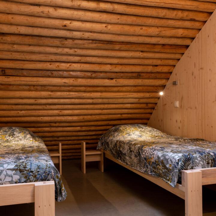 Slaapkamer met twee losse bedden onder een balkenpalfond